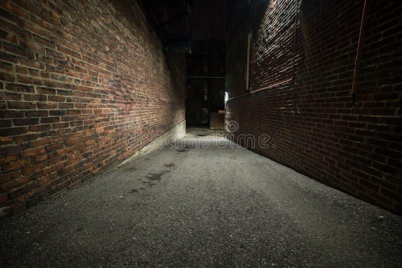 Vicolo scuro vuoto spaventoso con i mura di mattoni immagini stock