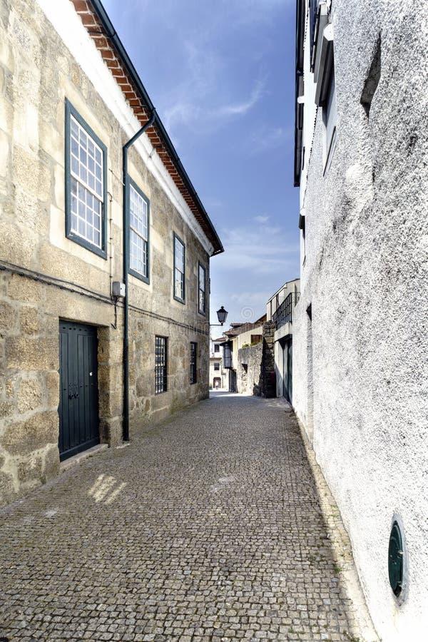 Vicolo stretto tipico pavimentato con i ciottoli e con le vecchie case di pietra nel centro di vecchia città di Guimaraes immagine stock