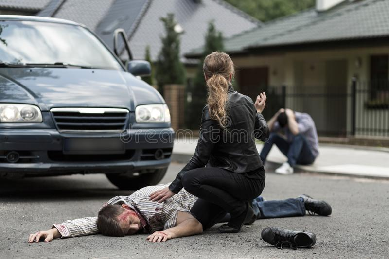 Victim of car accident. Bloody victim of car accident lying on the street stock photo