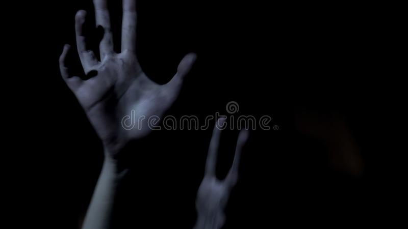 Victim hands stretching out in darkness, begging for help, scary thriller royalty free stock photos