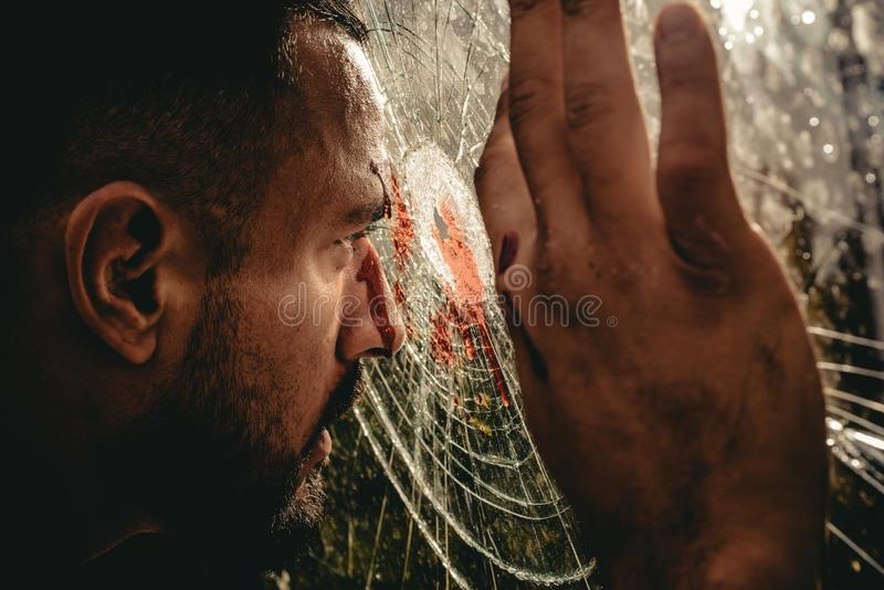 Victim of war. Wounded man victim looking through broken glass. Crime or violence victim. Victim of accident.  royalty free stock images