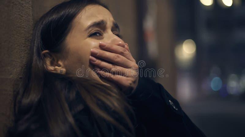Victime choquée de voleur pleurant à la rue de nuit, attaque de panique, traumatisme psychologique images stock