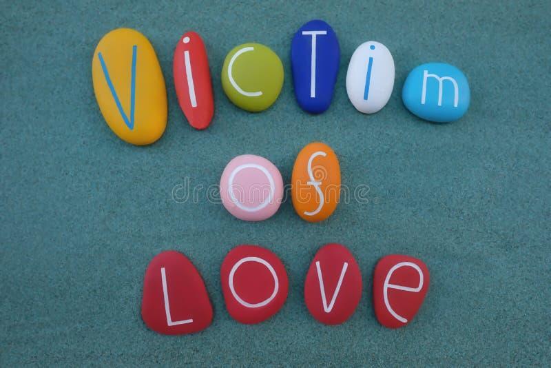 Victime de l'amour, composition artistique en textes avec les pierres colorées photographie stock libre de droits