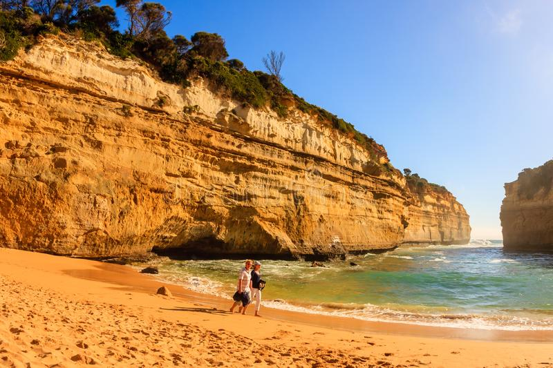 Victoria, Australia - January 06, 2009: People walking along sand beach. Loch Ard Gorge, Port Campbell National Park on Great royalty free stock images