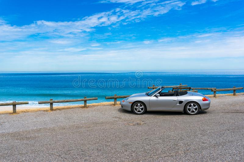 Silver Porsche convertible car with ocean on the background royalty free stock photography