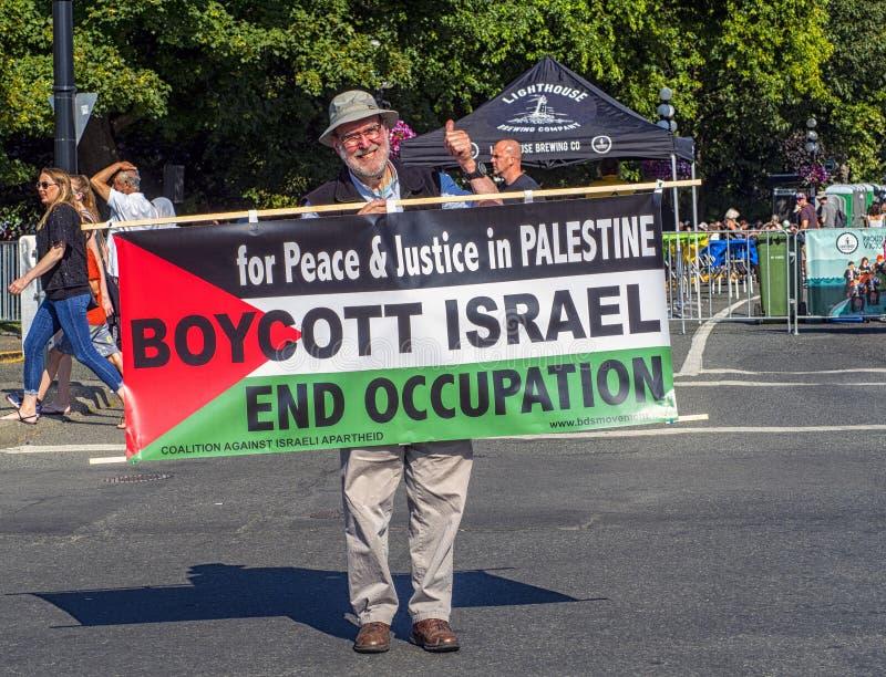 VICTORIA, CANADÁ 4 DE AGOSTO DE 2019: Suportes do homem em victoria do centro queguarda um sinal para a paz e justiça para Palest imagem de stock