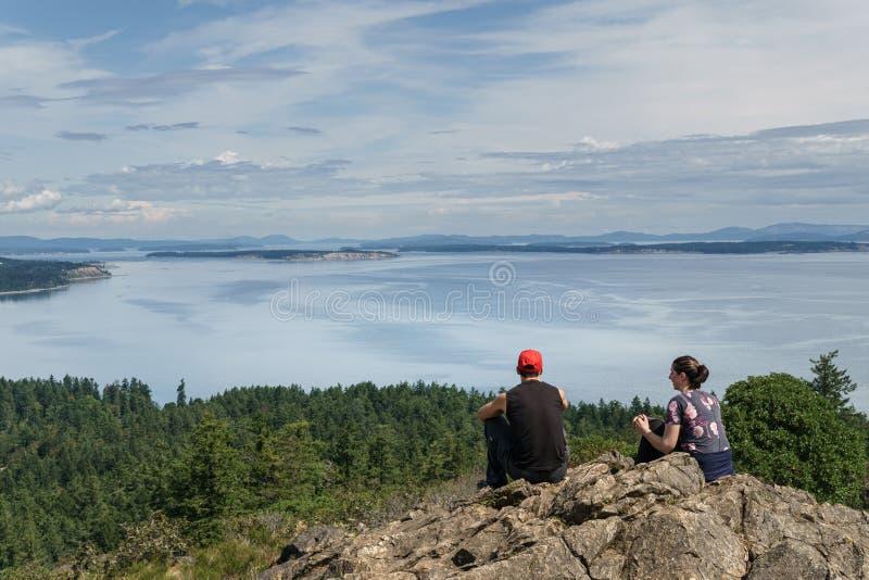 VICTORIA, CANADA - JULI 13, 2019: yang koppel bij de bovenkant van de berg aan een mooie Vreedzame Oceaanmening stock foto
