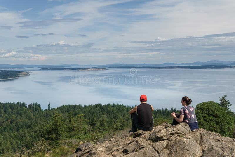 VICTORIA, CANADA - JULY 13, 2019: yang couple at the top of the mountain with a beautiful Pacific Ocean view stock photo