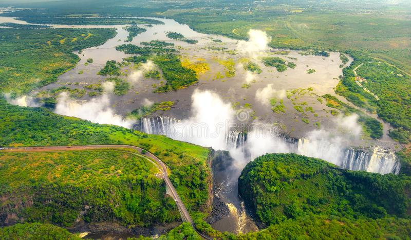 Victoria Falls in Zimbabwe and Zambia. Aerial helicopter photo, green forest around amazing majestic waterfalls of Africa. Livingston Bridge above the river royalty free stock image
