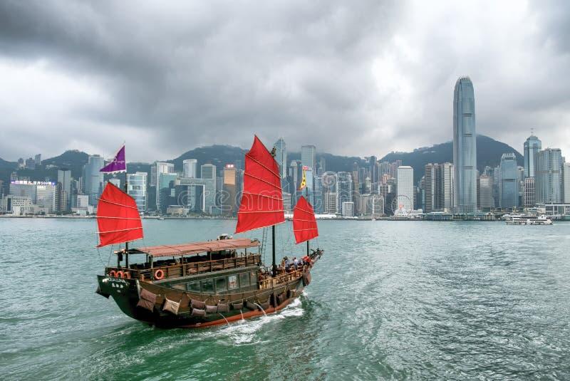 Iconic junk boat cruising around Hong Kong skyline stock image