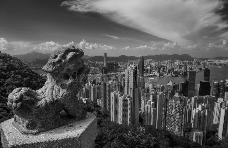 Victoria Harbour en Hong Kong vu de Victoria Peak avec la statue d'un lion chinois dans le premier plan photographie stock libre de droits