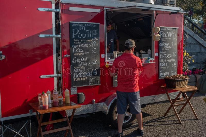 Victoria, het Eiland van Vancouver, Brits Colombia, Canada, 8 Juli, 2019: Een mens in een rood overhemd dat van een Re-voedsel op royalty-vrije stock foto
