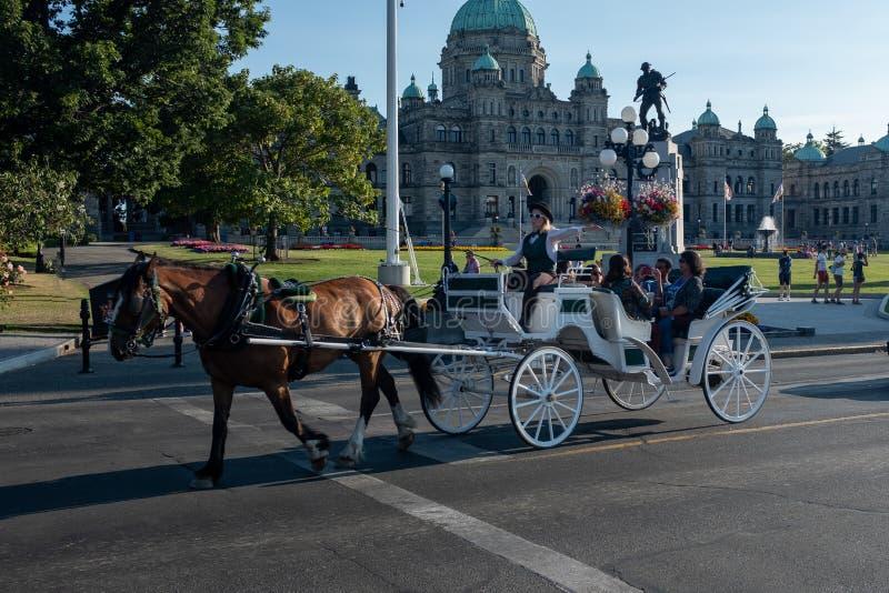 Victoria, isla de Vancouver, A.C., Canadá agosto, vigésimo sexto, 2018: Un carro traído por caballo con los turistas pasa al p foto de archivo libre de regalías