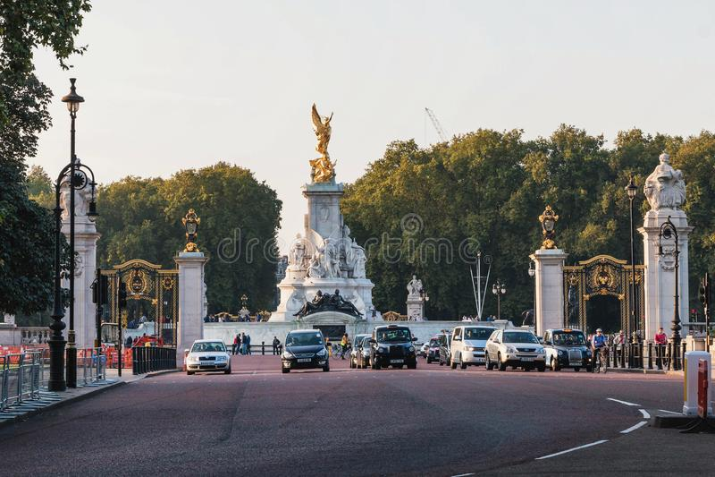 Victoria Memorial in London. Busy day with people and cars on the street. Editorial royalty free stock photo