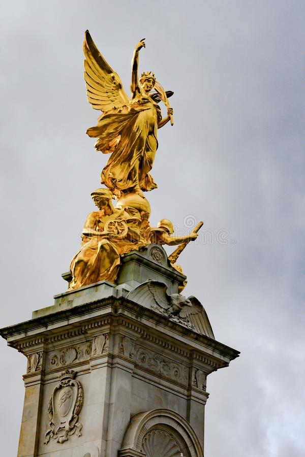 Victoria memorial London, Victory statue, England. People waiting in front of gates of Buckingham Palace royalty free stock photo