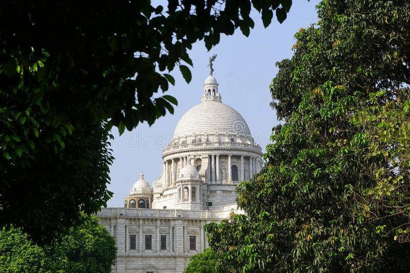 The Victoria Memorial in sub frame of the tree. The Victoria Memorial one of most famous monuments of India, situated at heart of the City of Joy, Kolkata royalty free stock images