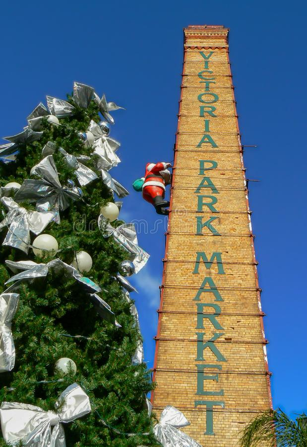 Victoria Park Market at Christmas time, Auckland, New Zealand. Santa Claus climbing the Victoria Park Market tower next to a big decorated christmas tree stock image