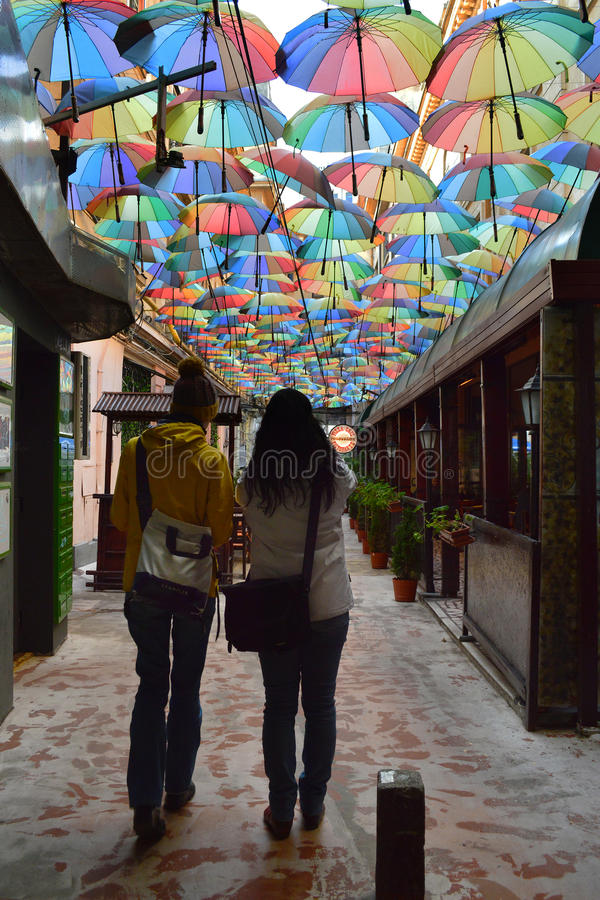 Victoria passage, Bucharest, Romania. Bucharest, Romania - October 29, 2016: Two young women in the covered by colorful umbrellas Victoria passage known with its royalty free stock images