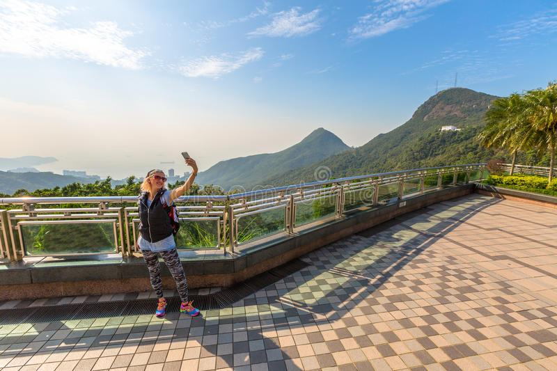 Victoria Peak Galleria. Young, smiling and fashionable tourist takes selfie on the popular free viewing terrace overlooking Victoria Peak Galleria that on the stock photo