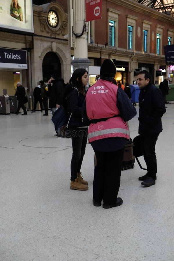 Victoria Rail Station-werknemer die twee mensen helpen royalty-vrije stock fotografie