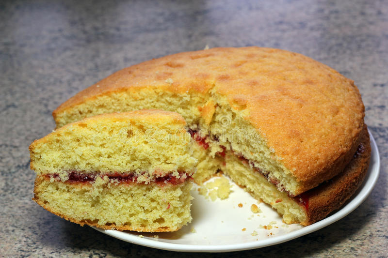 Victoria sponge cake. Separate piece cut off. A victoria sponge cake on a plate with a piece of cake cut off. Sponge cake with jam or jelly between the layers stock image