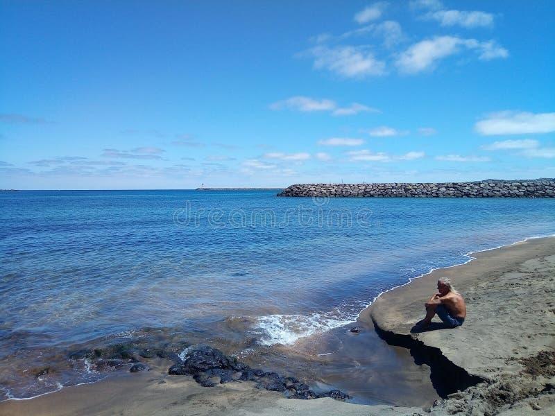 Victoria-strand bij Terceira-Eiland, de Azoren, Portugal met de meditatieve man dichtbij het water royalty-vrije stock afbeelding