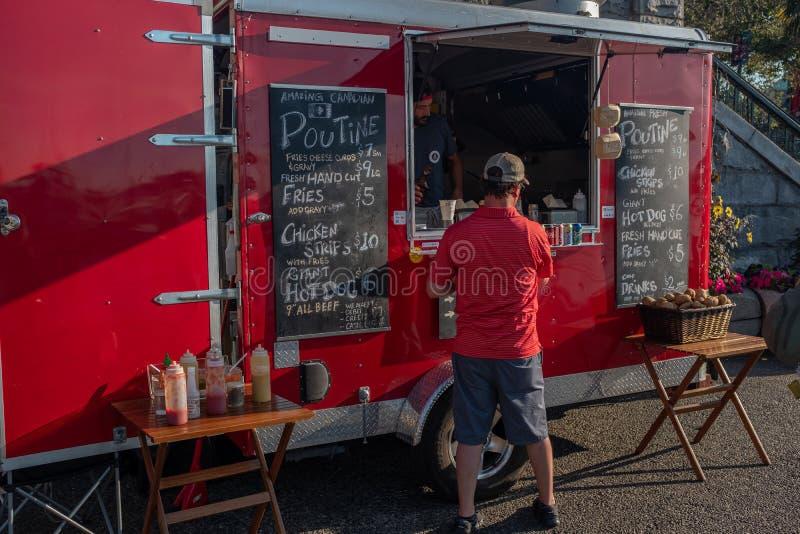 Victoria Vancouver ö, British Columbia, Kanada, Juli, 8, 2019: En man i en röd skjorta som beställer från en beträffande mat, sta royaltyfri foto