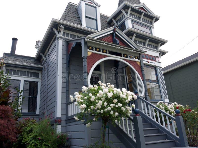 Victoriaans huis met witte roze struik vooraan stock fotografie