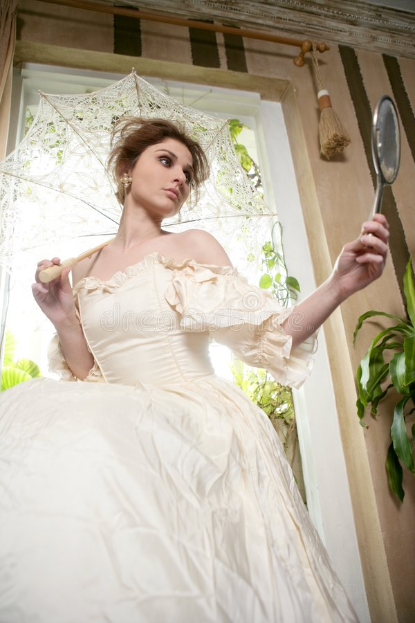 Victorian beautiful woman, white dress at home. Looking hand mirror stock photos