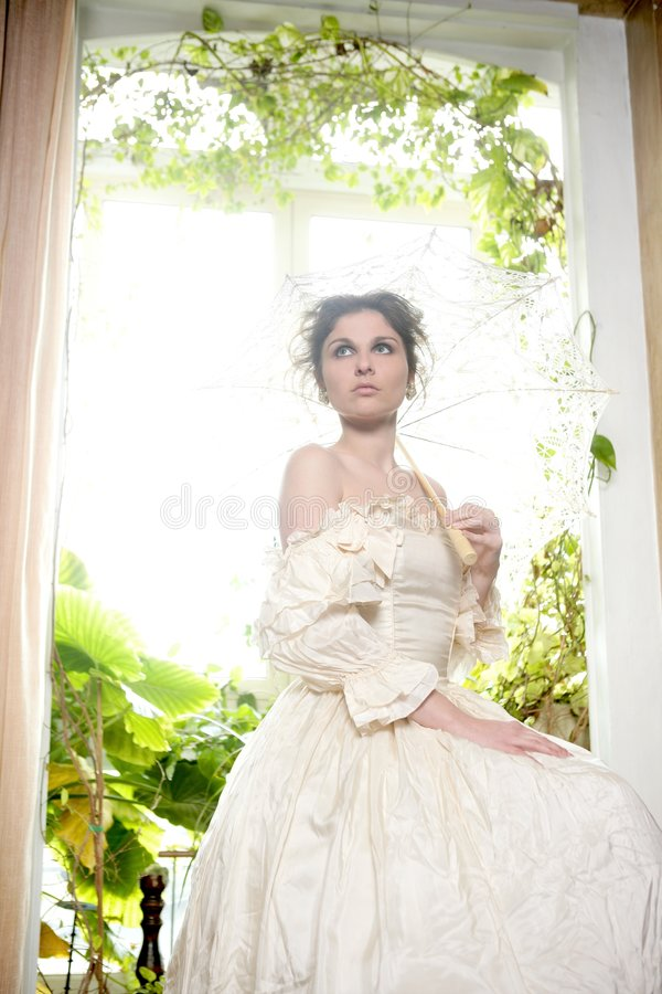 Victorian beautiful woman, white dress at home. Window with plants royalty free stock photos