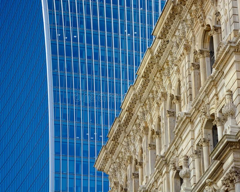 Architecture old and new in the city. A Victorian decorative stone building built by skilled craftsman is dwarfed by a modern 21st century all glass office tower stock images