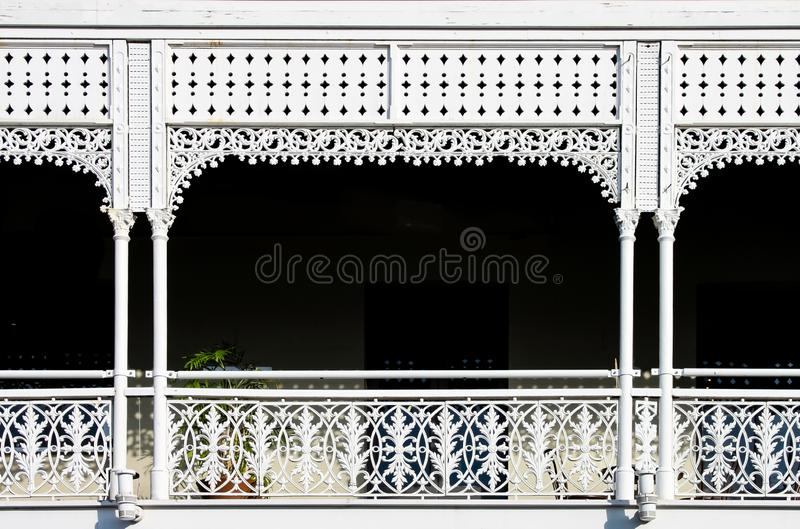 Victorian decorative wrought iron balcony with a plant on it but mostly darkness behind the white painted ornate railings - stock photo
