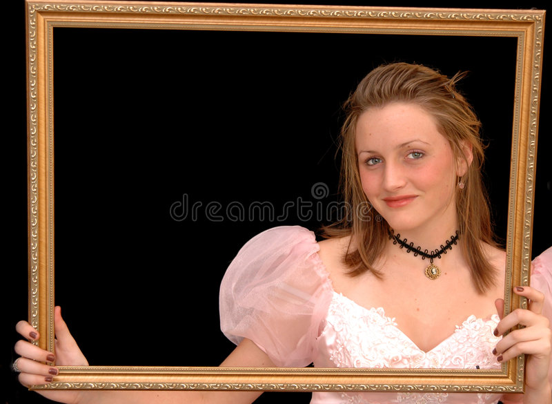 Victorian girl in frame. Portrait of a girl in a victorian dress and necklace holding a gold picture frame royalty free stock image