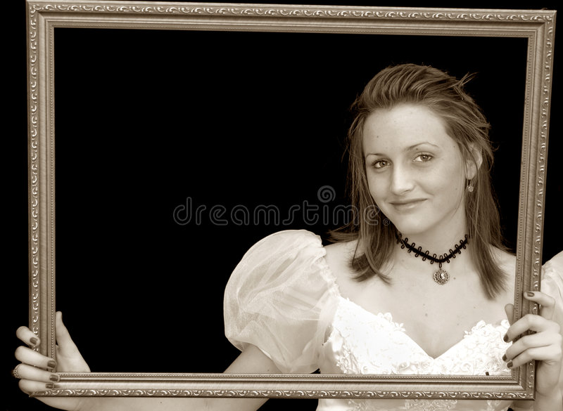 Victorian girl portrait. Portrait of a girl in a victorian dress and necklace in sepia holding a picture frame stock photo
