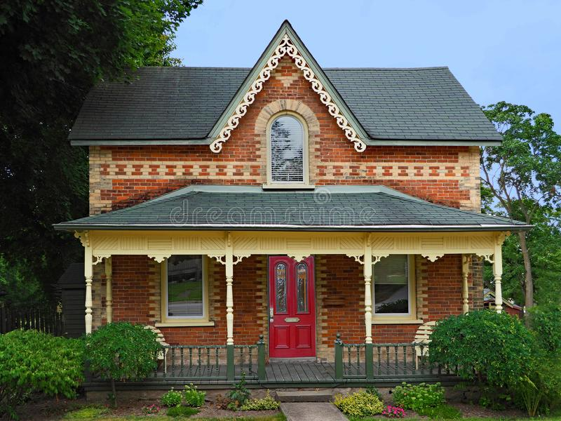 Victorian Gothic style farm house. With multicolored bricks and full width porch royalty free stock photo