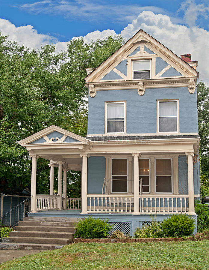 Victorian Home. Victorian style brick home painted blue with cream trim after a rain in springtime royalty free stock images