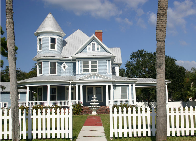 Victorian Home. Blue Victorian home with white trim and bordered by picket fence stock photography