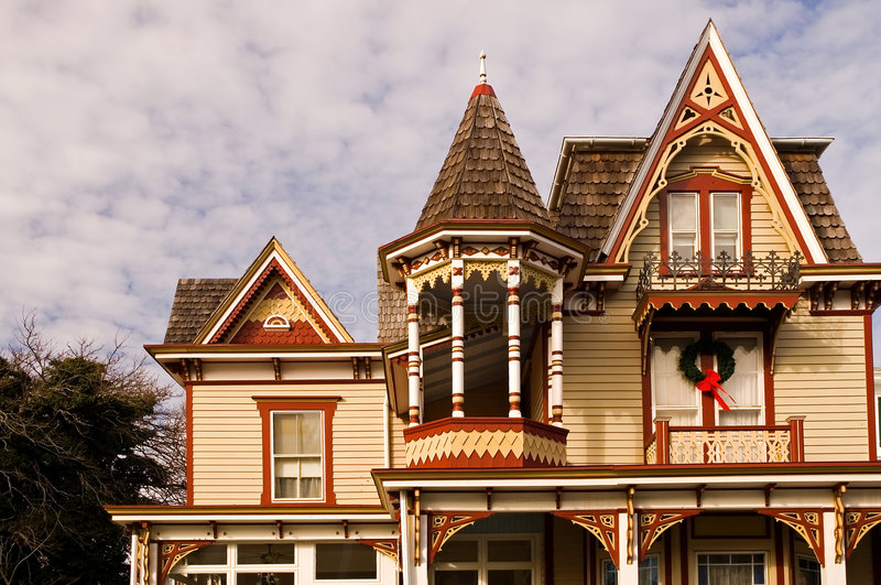 Victorian house at Christmas. Yellow Victorian House with red and white gingerbread trim decorated for Christmas with a wreath royalty free stock images