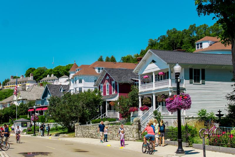 Victorian house lining the streets of Mackinac Island near downtown as tourists walk by in the summer stock photo