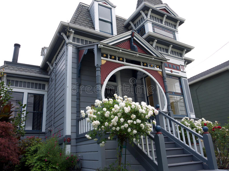 Victorian house with white rose bush in front