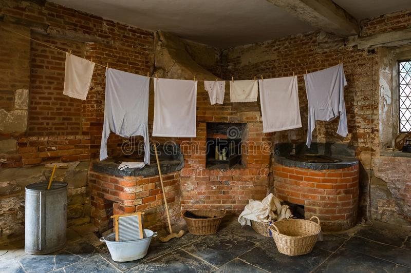 Victorian laundry room with equipment. Clothes drying on a line in a laundry room.Victorian laundry room with vintage equipment stock photography