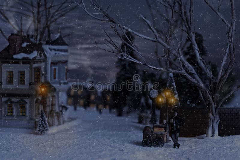 Victorian man selling chestnuts in village at christmas. While it is snowing stock images