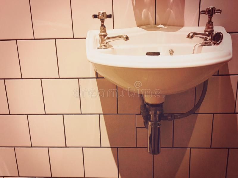 Victorian sink and bathroom. Tiled wall and sink royalty free stock image