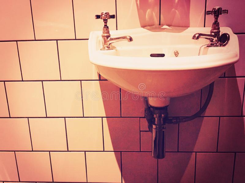 Victorian sink and bathroom. Tiled wall and sink stock photography