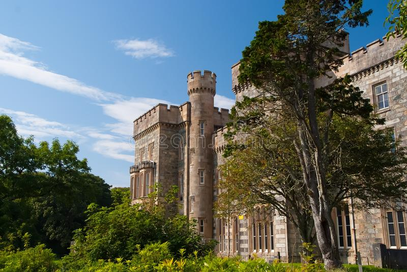 Victorian style architecture and design. Lews Castle in garden of Stornoway, United Kingdom. Castle with green trees on. Blue sky. Landmark and attraction royalty free stock photos