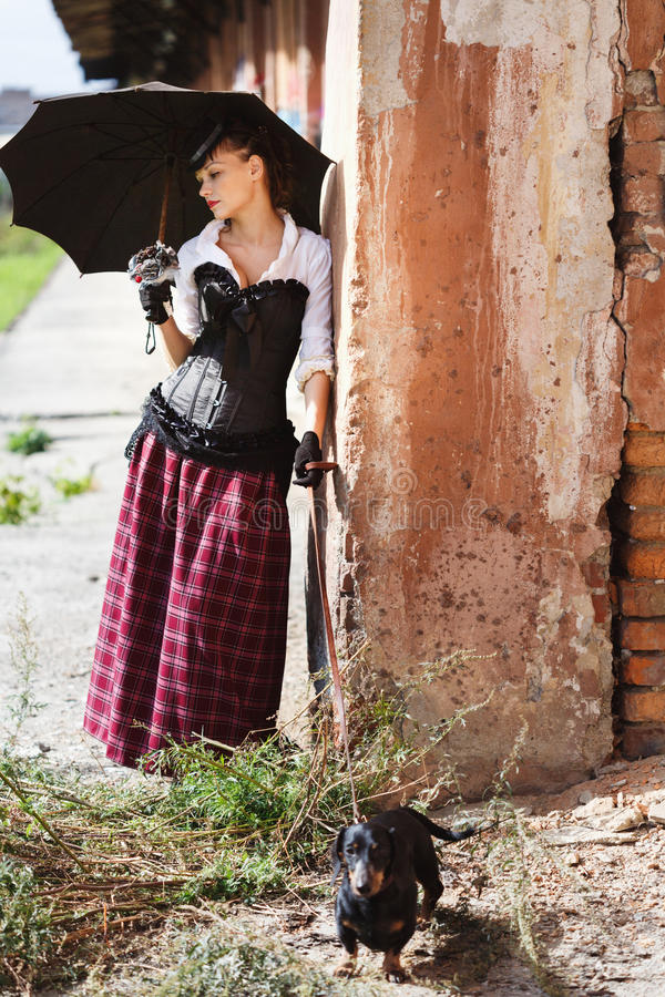 Victorian styled model posing near wall stock photography