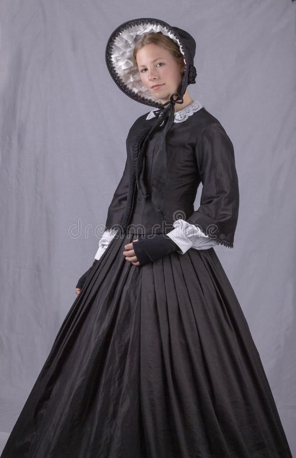 Victorian woman in black bodice. bonnet and skirt. Victorian woman in a black bodice, bonnet and skirt against a plain studio backdrop royalty free stock photo