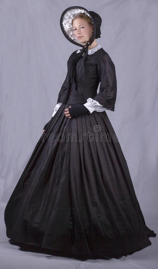 Victorian woman in black bodice. bonnet and skirt. Victorian woman in a black bodice, bonnet and skirt against a plain studio backdrop stock image