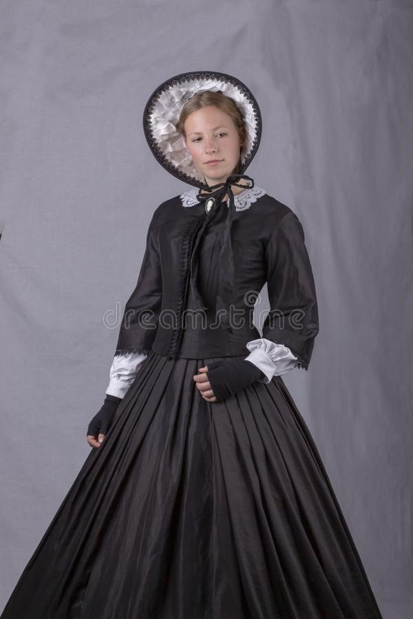 Victorian woman in black bodice. bonnet and skirt. Victorian woman in a black bodice, bonnet and skirt against a plain studio backdrop stock images