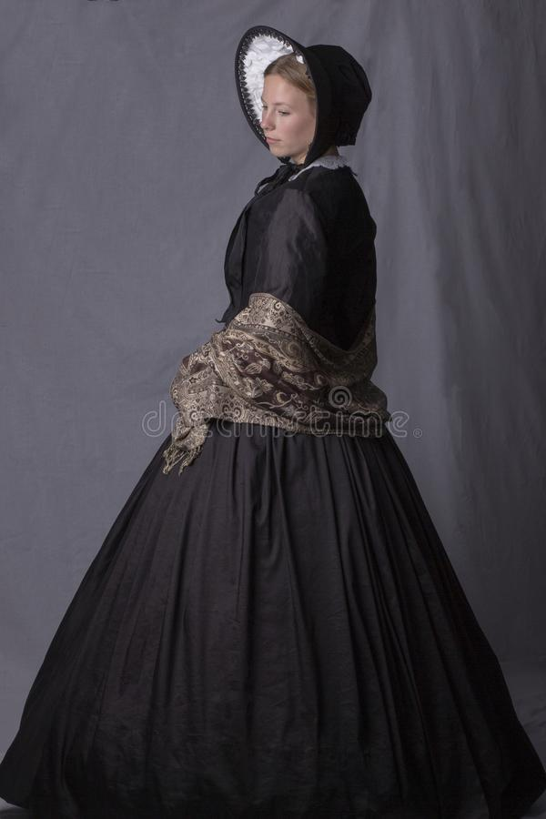 Victorian woman in a black bodice, shawl and bonnet. On a studio backdrop stock image